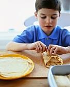 Boy filling pancakes