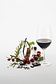 Glass of red wine and various aromatic ingredients