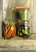 Carrots, peas and gherkins in three preserving jars