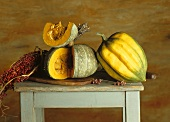 Pumpkins, one whole and one with a piece removed, on small table