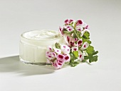 Home-made skin cream in glass jar, flowers beside it