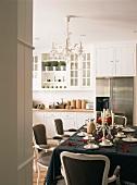 Ein festlich gedeckter Esstisch mit Barockstühlen in einer weissen Landhausküche
