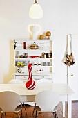 weiße Küche mit einem bunt gefüllten Buffetschrank hinter einem einfachen Holztisch