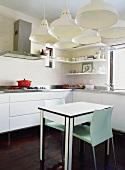 Gleich sechs Hängelampen beleuchten den kleinen kleinen, schlichten Esstisch in der modernen Küche