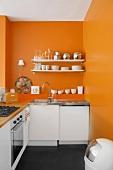 Leuchtendes Orange an der Wand wertet die schlichte weisse Küchenzeile auf