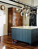 Diverse Töpfe über einem Küchenblock im Landhausstil, dahinter ein schöner, antiker Holzschrank