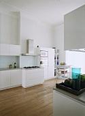 Eine puristische Designerküche mit Dielenboden und Stuckdecke