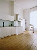 Eine moderne Küchenzeile mit weissen Schrankfronten im Altbau mit Dielenboden, Stuckdecke und großem, raumhohem Fenster