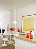 weiße Esszimmergarnitur im Retrostil vor einem gelben Gemälde im hellen, modernen Esszimmer