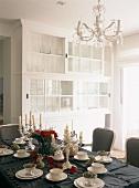Der gedeckte Esstisch mit schwarzer Tischdecke und roten Rosen kontrastiert den romantischen, weissen Vitrinenschrank und Kronleuchter