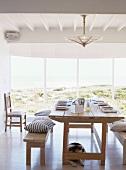 Das Panoramafenster bietet vom rustikalen Holztisch mit Sitzbänken aus einen traumhaften Blick auf die Umgebung