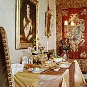 Gedeckter Esstisch mit Seidentischdecke im prunkvollen Esszimmer mit Wandteppich und Barockgemälden