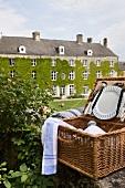 Ein geöffneter Picknickkorb im Vordergrund, dahinter ein altes Herrenhaus im englischen Stil mit efeuberankter Fassade