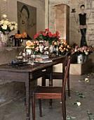 Diverse Rosensträusse und ein antiker Holztisch und -stuhl in einem Raum mit bemalten Wänden