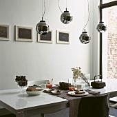 Verspiegelte Kugelleuchten über einem modernen, gedeckten Frühstückstisch