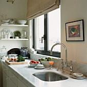 Ausschnitt einer Küchenzeile mit Marmoroberfläche und eleganter Spülarmatur