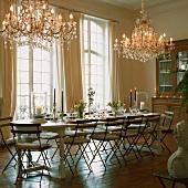 Gedeckter Landhaustisch mit Klappstühlen unter zwei prunkvollen Kronleuchtern in einem eleganten Saal mit raumhohen Fenstern