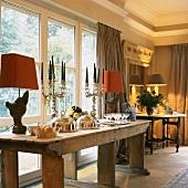 Edles Tafelsilber auf einem rustikalen, antiken Holztisch in einem eleganten Zimmer mit Stuckleiste und Fensterfront