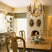 Einfacher Landhaustisch mit Kuchen und Teeservice unter einem antiken Kronleuchter
