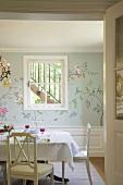 Blick auf einen gedeckten Esstisch vor einer Wand mit Sprossenfenster und floraler Wandmalerei
