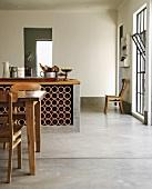 Küchentheke mit Weinregal in einem offenen Wohnraum mit Betonboden und Biedermeierstühlen