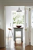 Blick in die Küche mit rollbarem Küchenblock und Designerbarhocker