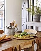 Gemischte Speisen und ein Besteckbehälter aus Blech auf einem rustikalen Esstisch
