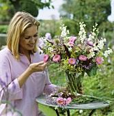 Frau erfreut sich an sommerlichen Blumenstrauss