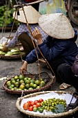 Vietnamese women selling fruit & vegetables at a street market