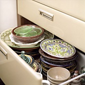 Cololurful crockery in a kitchen drawer
