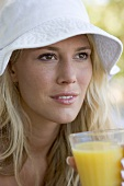 Woman in summer hat drinking a glass of orange juice
