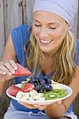 Frau isst Melone von einen Obstteller