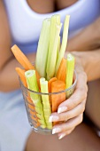 Woman's hand holding a glass of fresh vegetable sticks