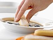 Making tiramisu: dipping a sponge finger in espresso