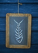 Picture symbolising fish: fish bones & head drawn on slate