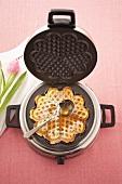 Lemon waffle with maple syrup in waffle iron