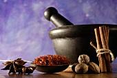 Star anise, saffron, nutmegs, cinnamon, mortar in background