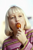 Blond girl sucking a lollipop