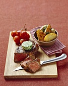 Beef steak with herb butter, roast potatoes, tomatoes