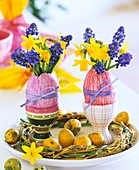 Narcissi and grape hyacinths in eggshell vases