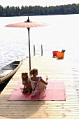 Woman with glass of strawberry Prosecco & dog on landing stage