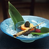 Salmon tartare with caviar in a small bowl, bamboo leaves