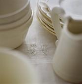 Weisses Geschirr auf Tischdecke mit gestickten Initialen