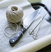 Kitchen utensils: ball of string, knife, skewers, baking parchment
