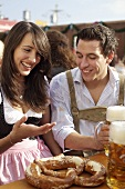 Young man & woman in traditional dress with pretzel, beer at fair