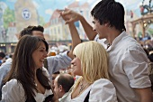 Cheerful young people in traditional dress at Bavarian fair