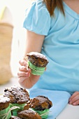 Girl holding blueberry muffin sprinkled with icing sugar