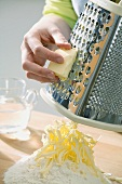Making shortcrust pastry: grating butter on to heap of flour