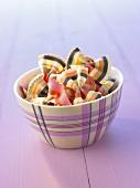 Multicoloured bow-tie pasta (farfalle) in a small bowl