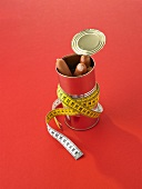 Frankfurters in a tin with a tape measure wrapped around it